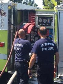 Engineer A. Wilson works on setting the pump up while Deputy Chief Randolph evaluates his performance.